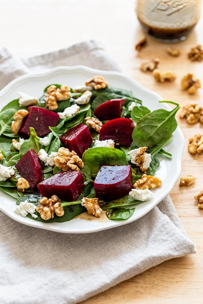 Layer cooked beets, goat cheese, and walnuts on top of fresh spinach with an easy balsamic dressing. The perfect salad for any time of year.