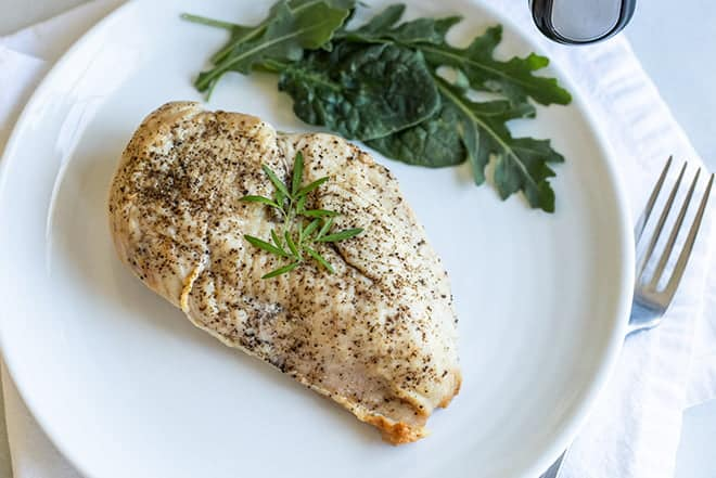 Seasoned chicken breast on a white dinner plate.