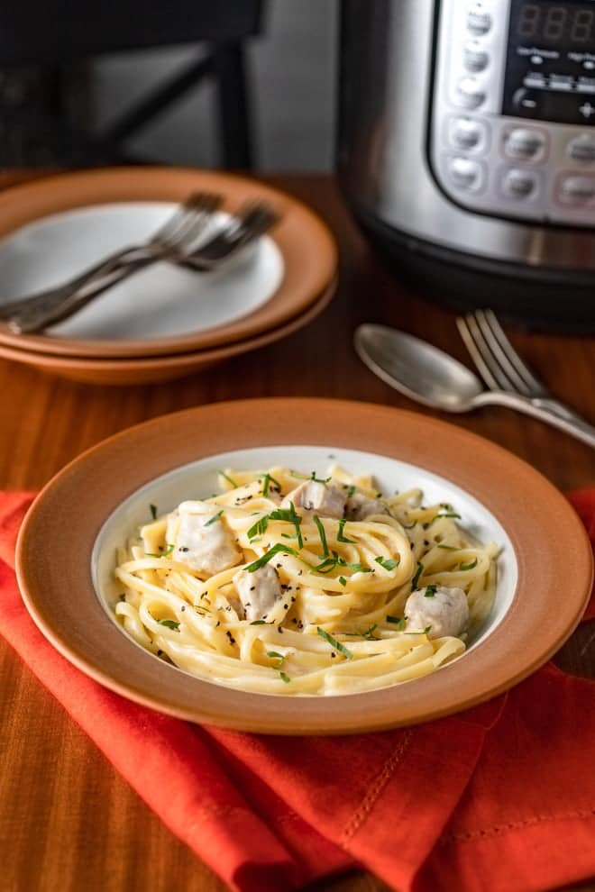This creamy, garlicky Instant Pot Chicken Alfredo is a no-brainer one pot meal. All of the cooking, including the noodles, is done in the pot making getting dinner on the table and clean up a breeze.
