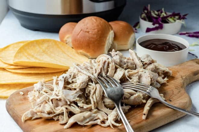 Pulled chicken and forks on cutting board, with tortillas, rolls, and bbq sauce in background.