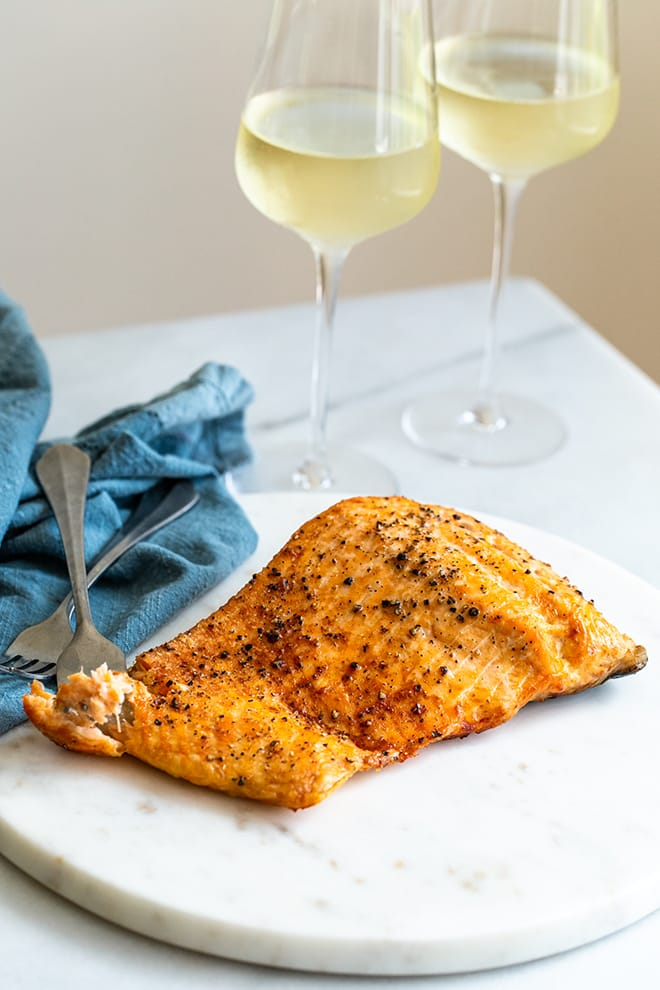 Crispy salmon on a marble plate with forks and a blue cloth napkin beside.