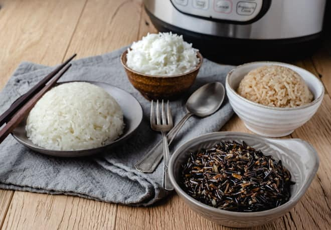Bowls of various types on rice in front of an instant pot.