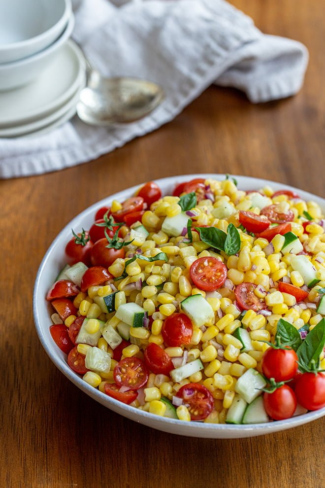 Bright and fresh corn salad is packed with fresh corn, tomatoes, cucumber, and basil. It's the perfect, refreshing side dish.