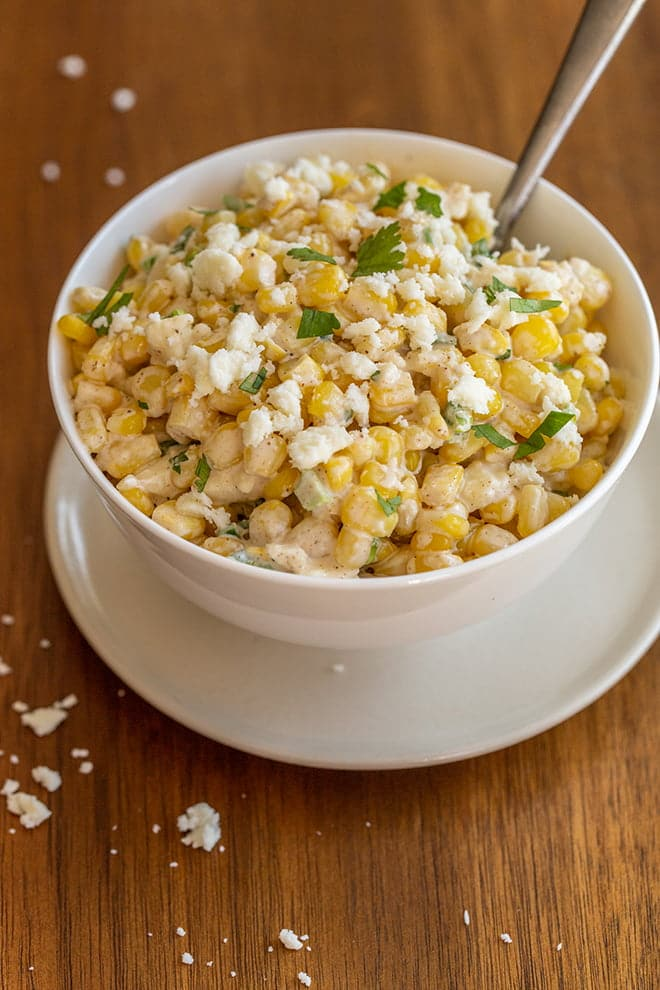 Mexican corn salad is like street corn in a bowl. Flavors of charred corn, cream, spices, cojita cheese and lime are mixed together for easy serving.