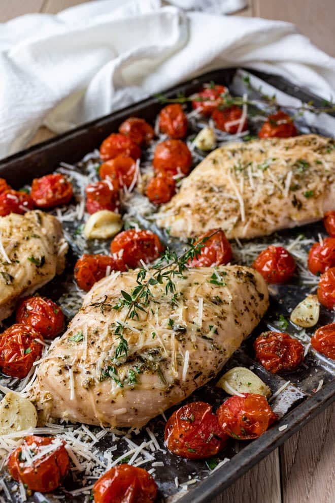 A mediterranean-inspired rub of basil, oregano, rosemary, and thyme flavors these baked Italian Chicken Breasts. Roasted garlic and cherry tomatoes compliment this easy sheet pan dish.