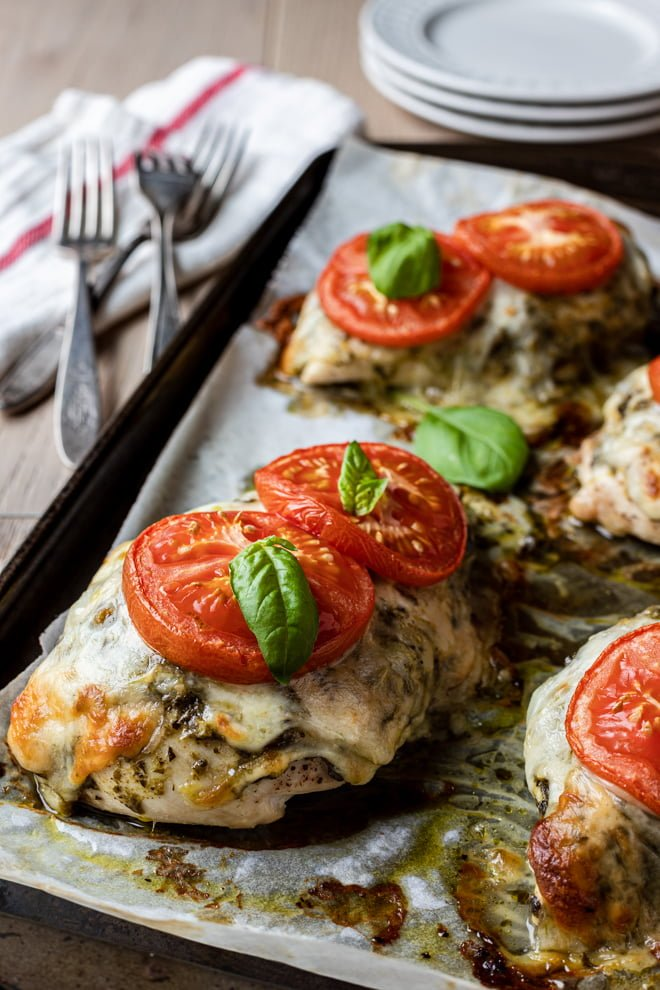 Pesto Chicken Breast topped with homemade or pre-packaged pesto, mozzarella and tomatoes is a weeknight show stopping dish.