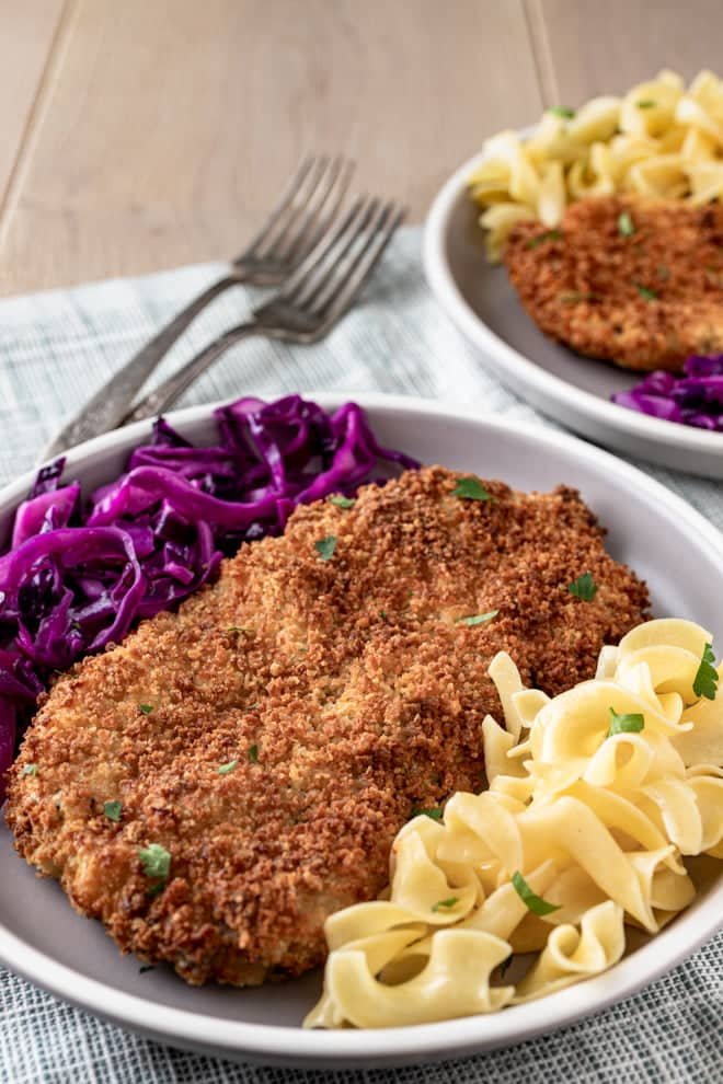 Breaded Pork Cutlets with buttered noodles and quick red cabbage sauerkraut on a dinner plate.