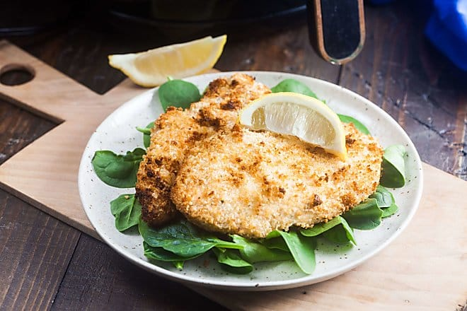 Two breaded chicken cutlets on a bed of baby spinach, topped with a lemon wedge.