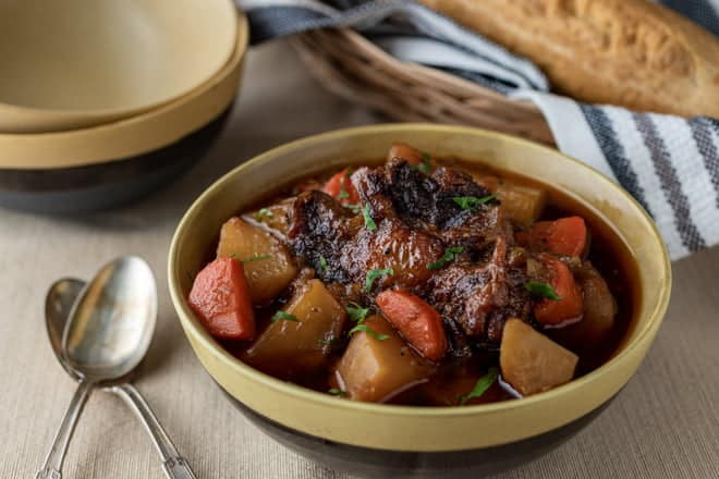 Oxtail Soup with carrots and potatoes in a deep brown bowl.