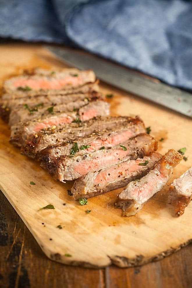Slices of broiled steak on a wooden board.