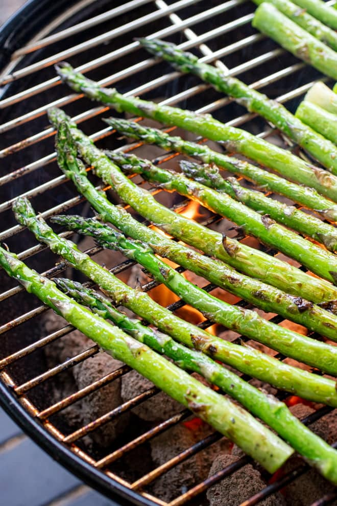 Asparagus cooking on a charcoal grill.