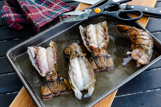 Lobster Tails cut open on a tray to prepare for the grill.