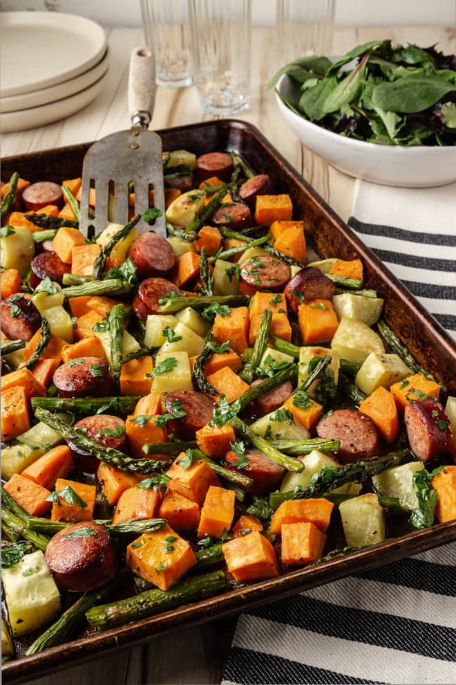This easy week-night sheet pan meal features sausage, sweet potatoes, and asparagus roasted to perfection and finished with a simple orange dressing.