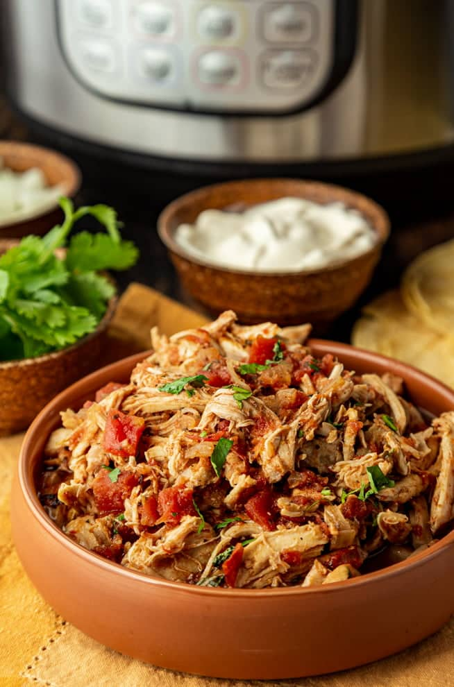 Shredded chicken with cooked tomato and cilantro in a terracotta bowl. There's a bowl of sour cream and an Instant Pot in the background.