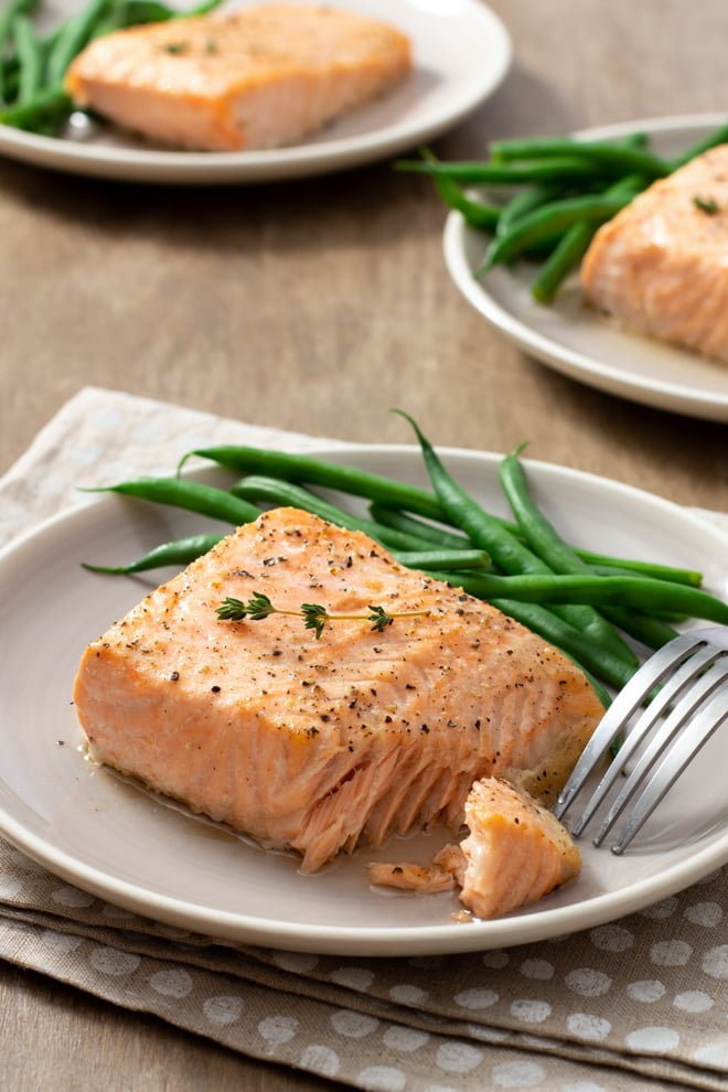 Cooked salmon fillet on white plate with green beans.