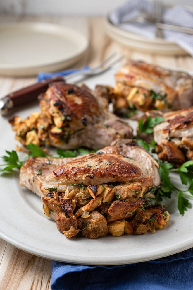 Pork chops stuffed with apples on a white serving plate.