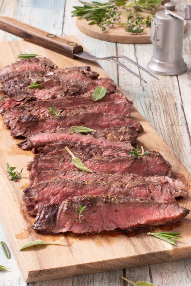Sliced skirt steak on wooden cutting board.