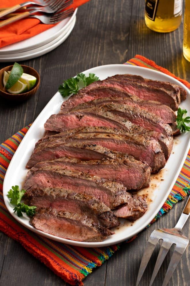 Cooked flank steak in slices on an oblong white platter.
