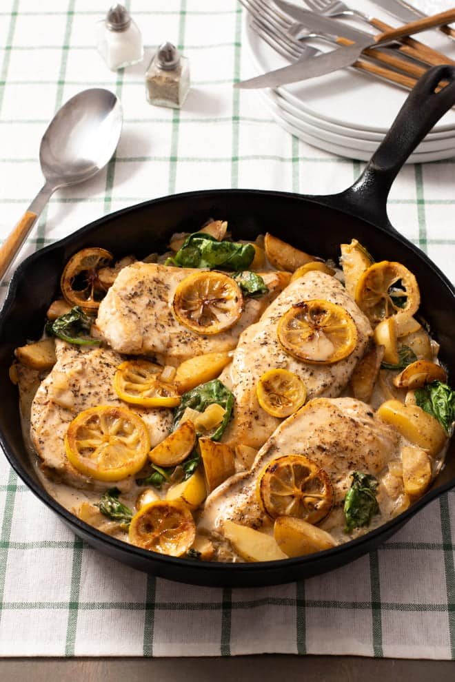 Cast iron skillet with chicken breasts, lemon slices, potatoes, and spinach.