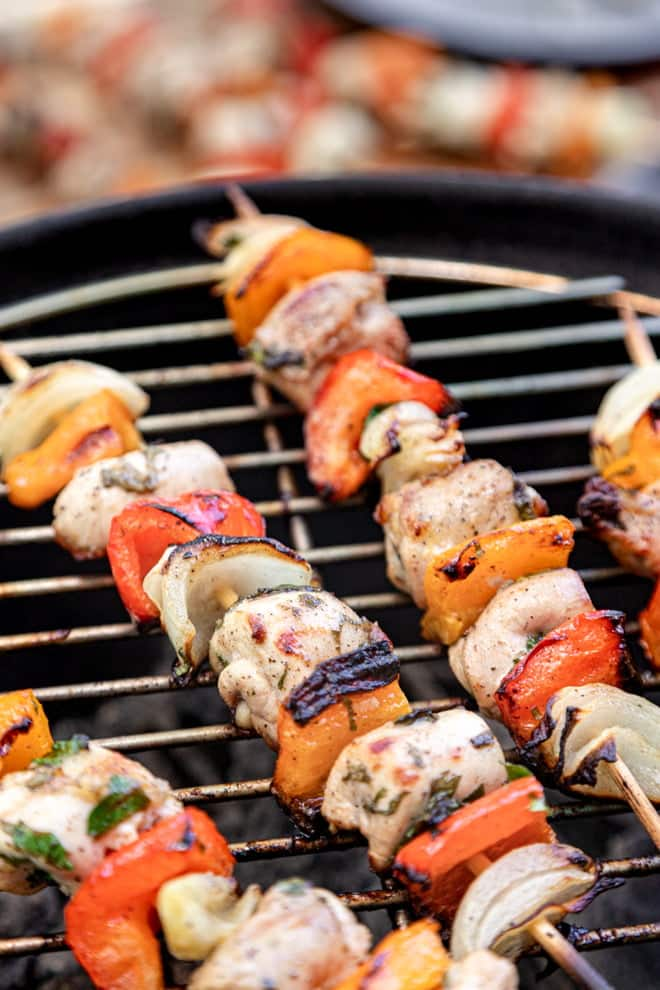 Skewers of chicken, bell peppers, and onion on a grill.