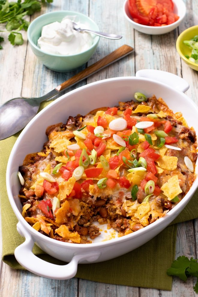 Casserole with ground beef and beans, topped with melted cheese, crushed tortilla chips, and fresh tomatoes and green onions.