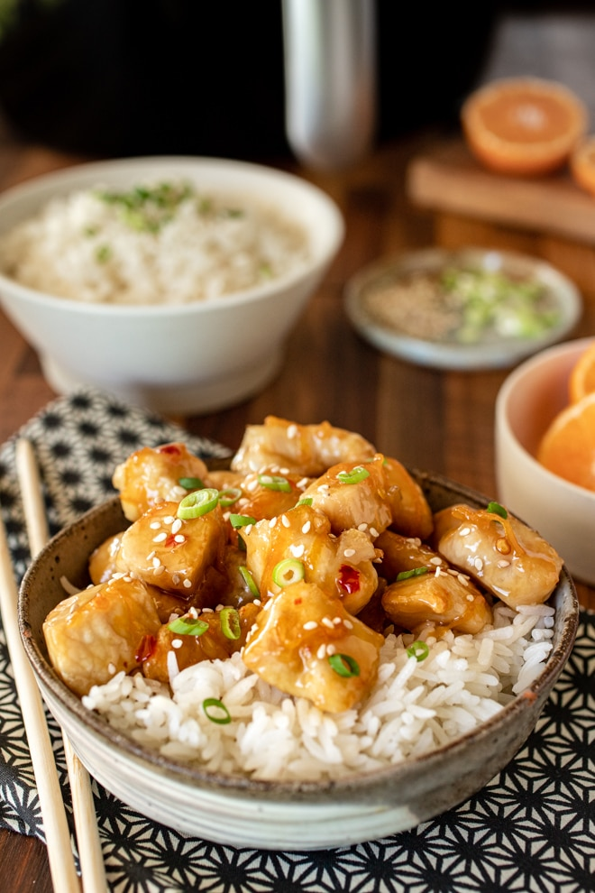 Orange chicken over white rice in a bowl. Bowls of rice and oranges in background.