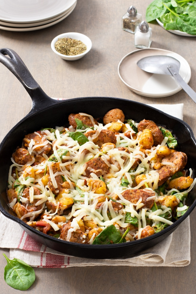 Cast iron skillet with sausage slices, gnocchi, spinach, and melting shredded mozzarella cheese.