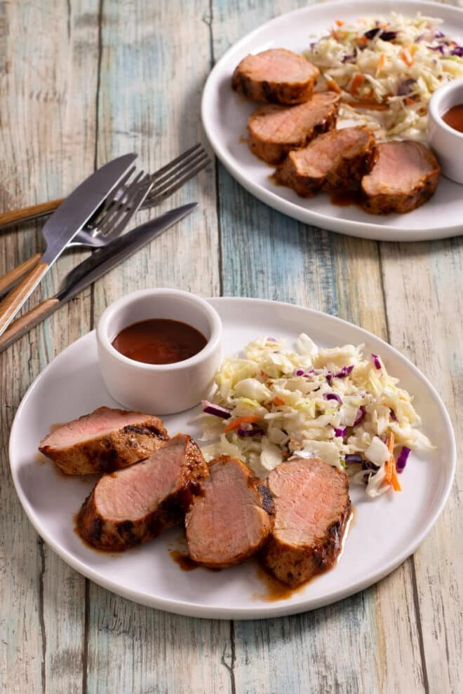 Sliced BBQ Pork Tenderloin on a white plate with coleslaw and BBQ sauce.