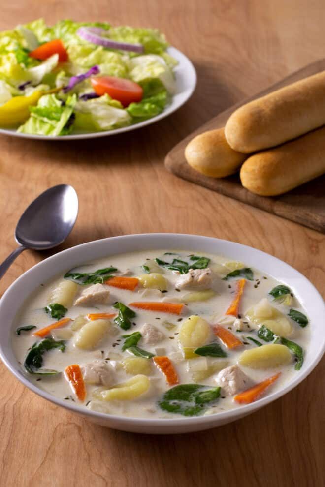 Chicken Gnocchi Soup with spinach and carrots in a creamy broth. Breadsticks and garden salad in background.