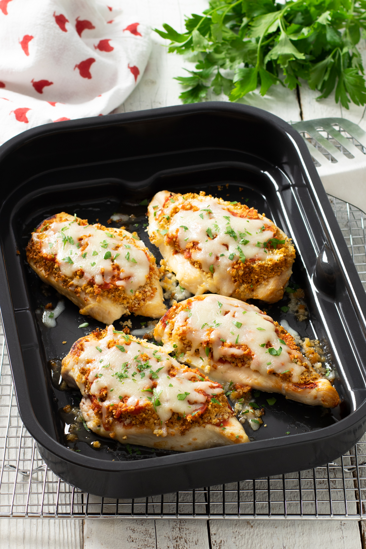 Four chicken breasts in an air fryer tray, topped with breadcrumbs, tomato sauce and melted mozzarella.