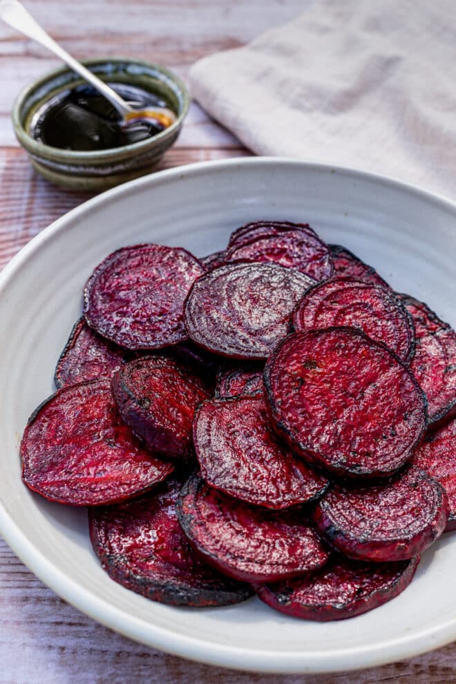 Grilled beet slices on a gray platter, with a small dish of balsamic glaze in the background.