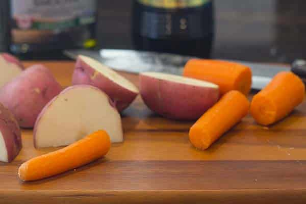 Large chunks of red potatoes and carrots on a cutting board