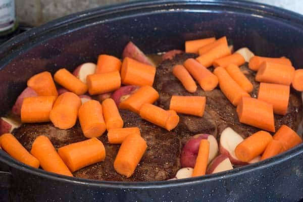 Carrots added on top of the roast and potatoes