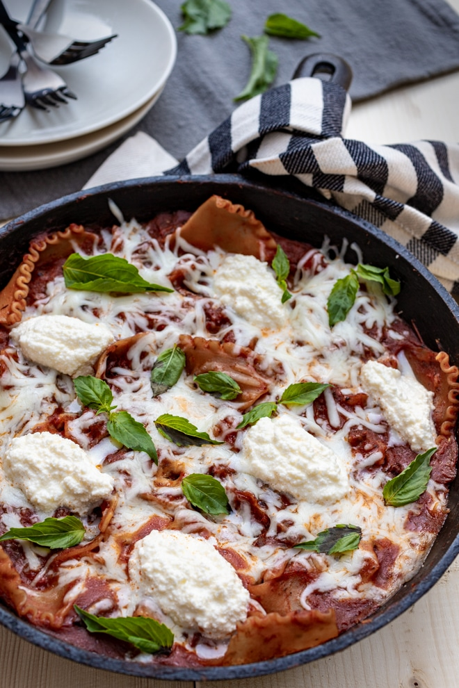 Skillet lasagna topped with dollops of ricotta cheese and fresh basil leaves.