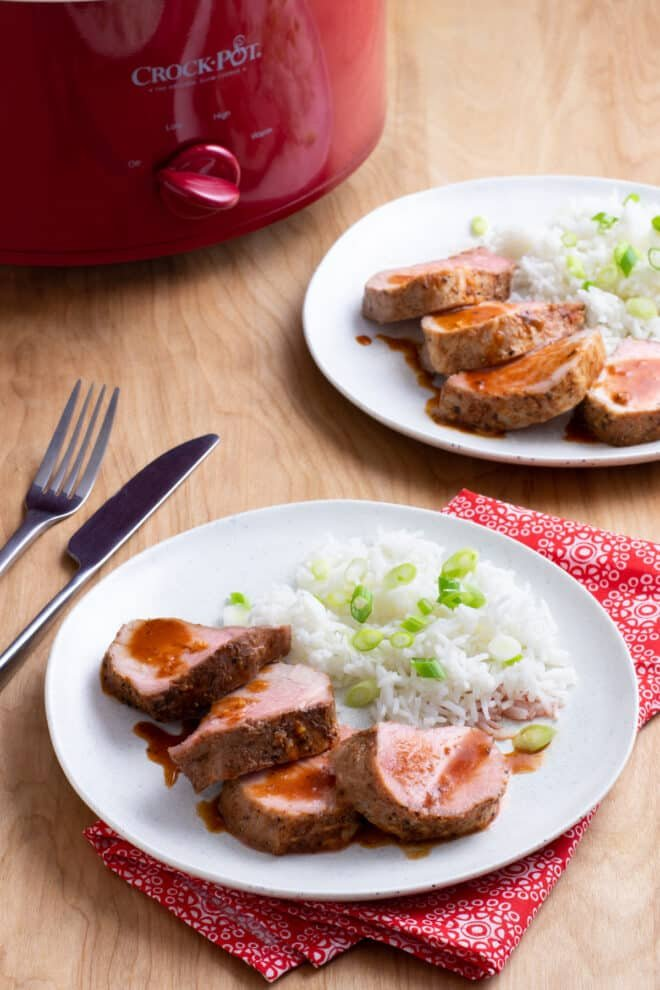 Slices of pork tenderloin with sauce on a white plate, with a side of white rice with green onion. Crock Pot in background.