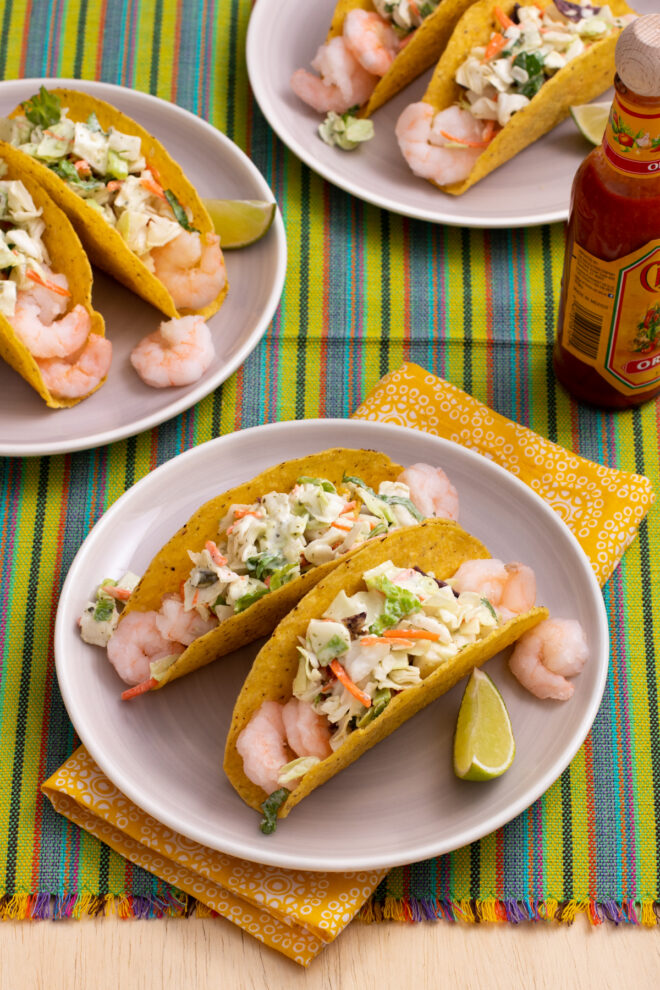 Shrimp and coleslaw salad in hard taco shells on plate with lime wedge. More plates of tacos and hot sauce in background.